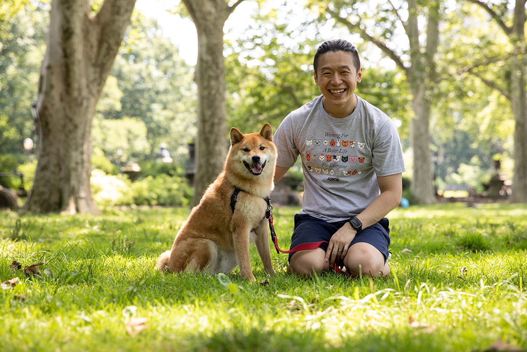 a man with a shiba inu in a park