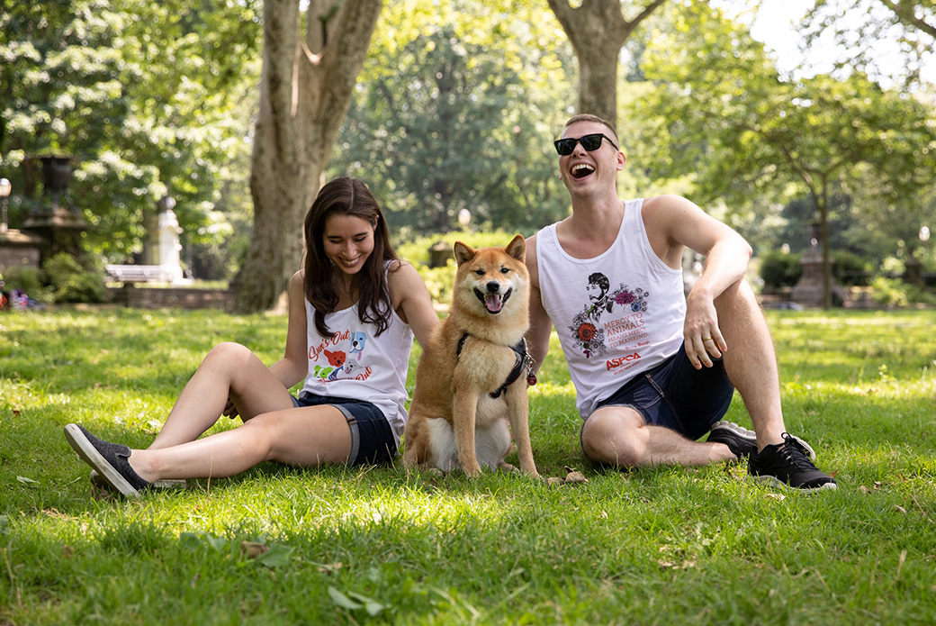 a woman and a man in shorts and tank tops in a park with a dog