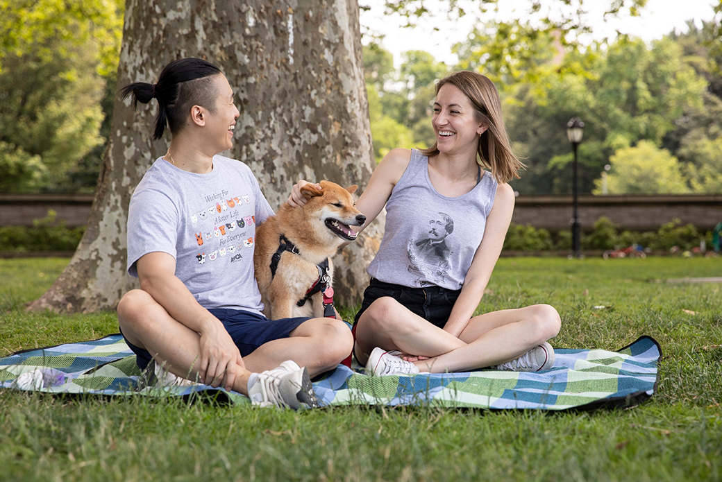 a man and woman on a picnic blanket with a Shiba Inu
