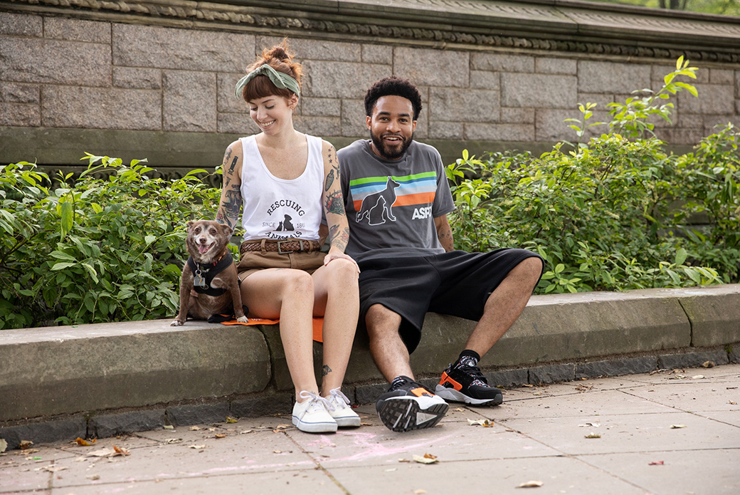a woman and man sitting with a rat terrier in the park