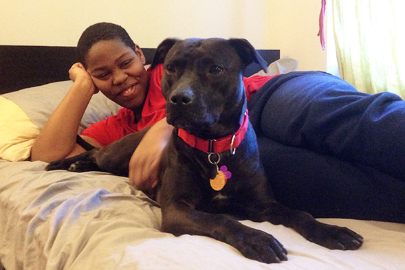 Young man lounging on bed with black dog