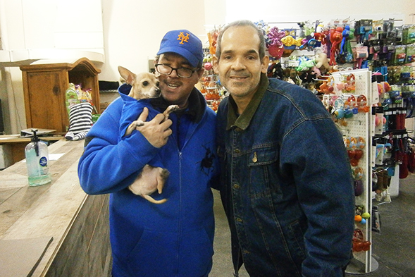 Two men smiling and holding a chihuahua