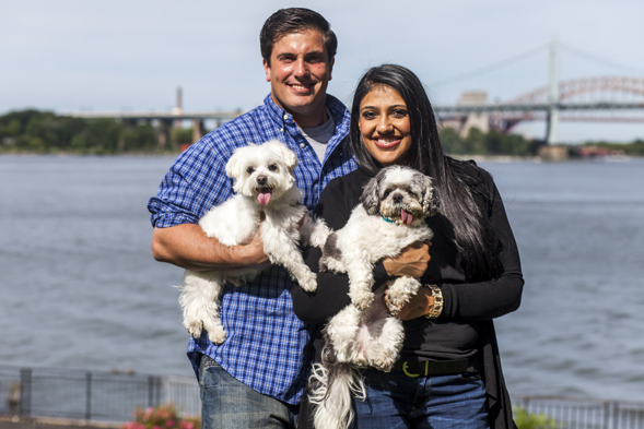 Happy couple smiling while holding two dogs