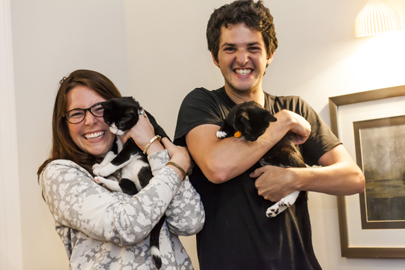 Two roommates holding black and white cats