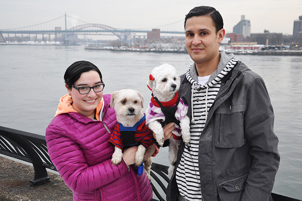 Young couple holding two white dogs