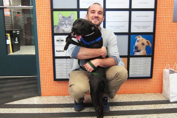 New adopter hugging black pit bull at ASPCA Adoption Center