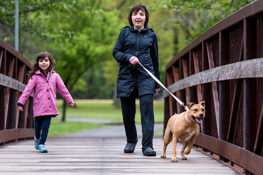 a woman walking a dog with her daughter over a bridge