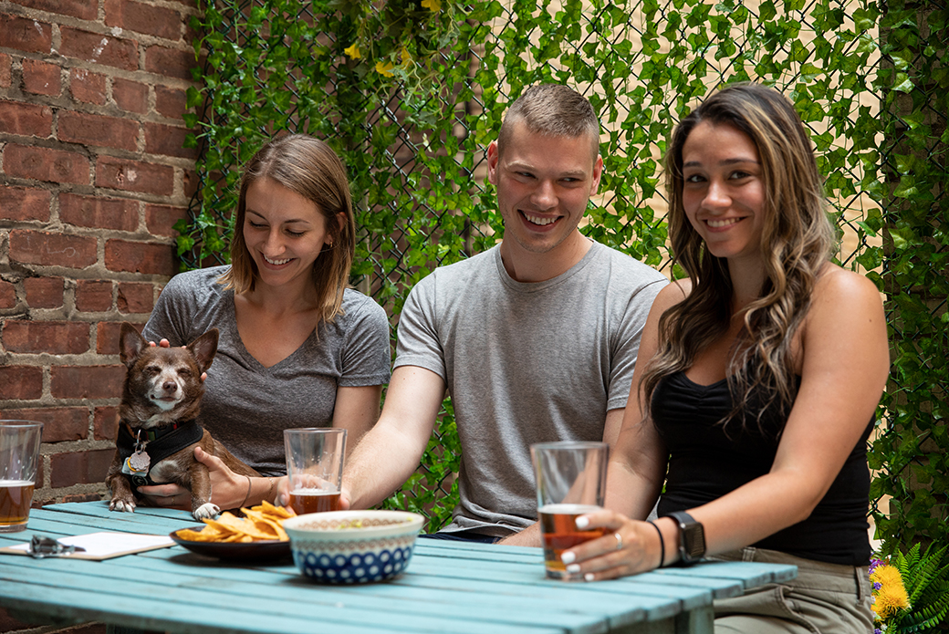 three people with a dog on a picnic table with drinks