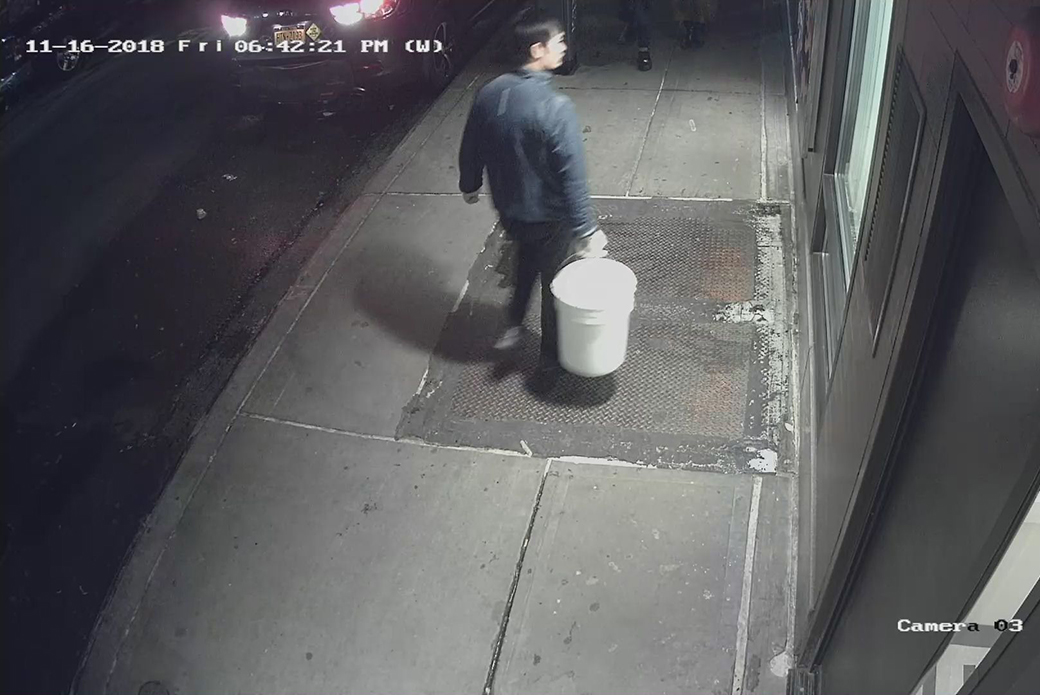 suspect carrying a sealed bucket with a cat in it