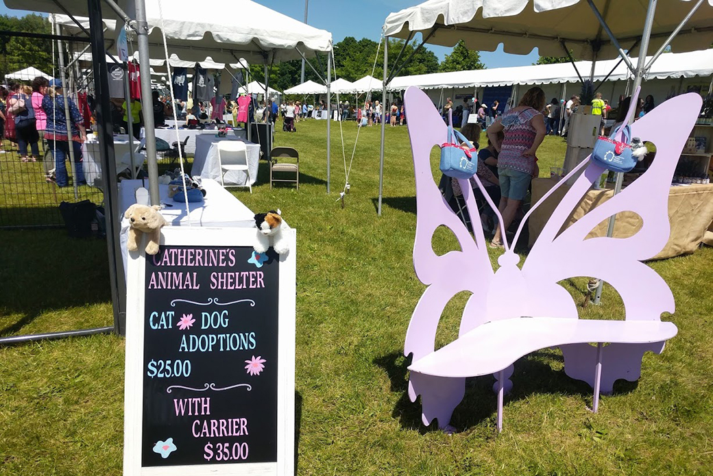 A sign for the event next to a lavender butterfly bench