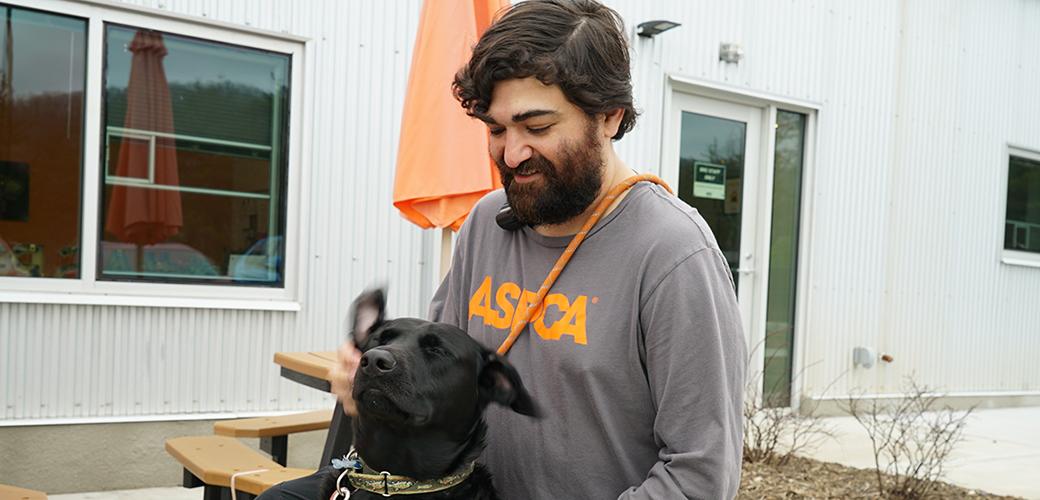 ASPCA staff member with a black dog