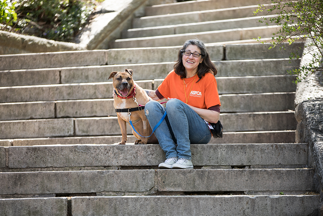 a woman with a dog sitting on stone steps outside