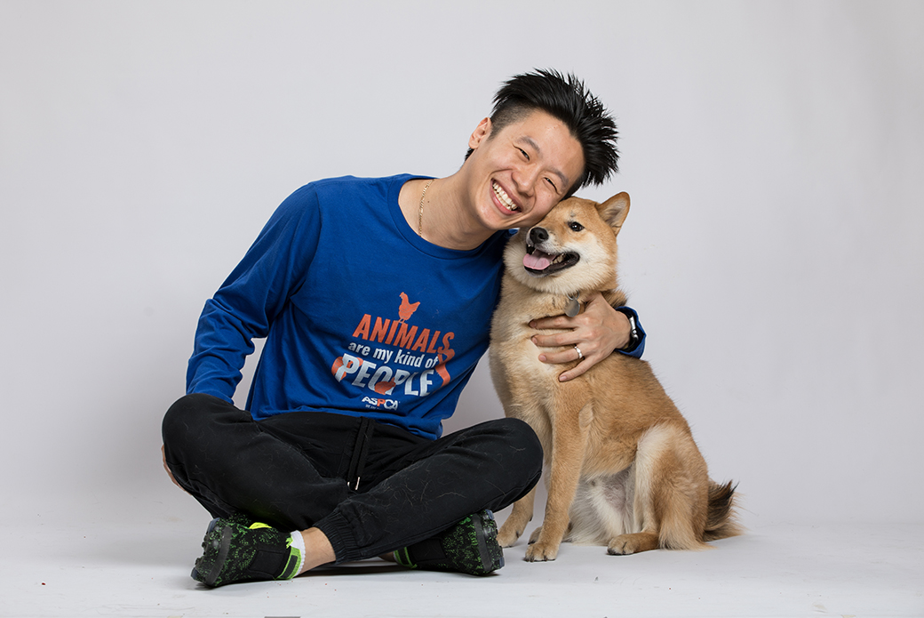 a man wearing an aspca sweatshirt with a Shiba Inu