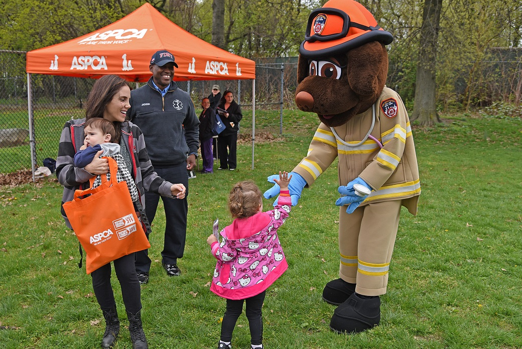 Lauren Hecht, with son Jonah, watches her daughter Samantha give the FDNY's life safety mascot, EMT Siren, a high-five.