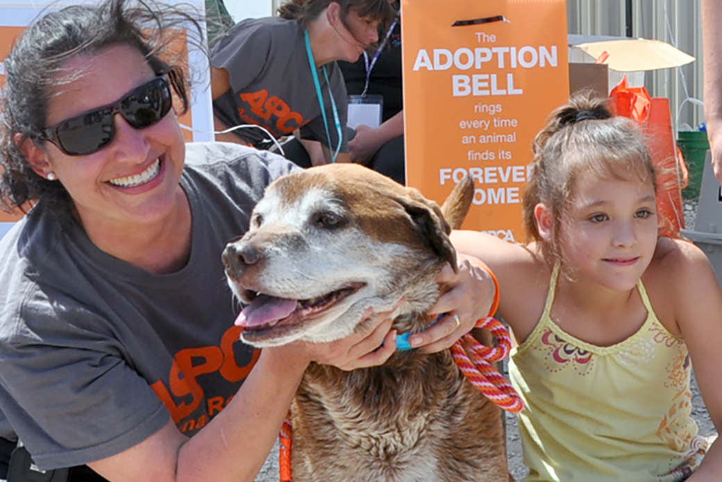 a girl with her rescued dog and an aspca responder