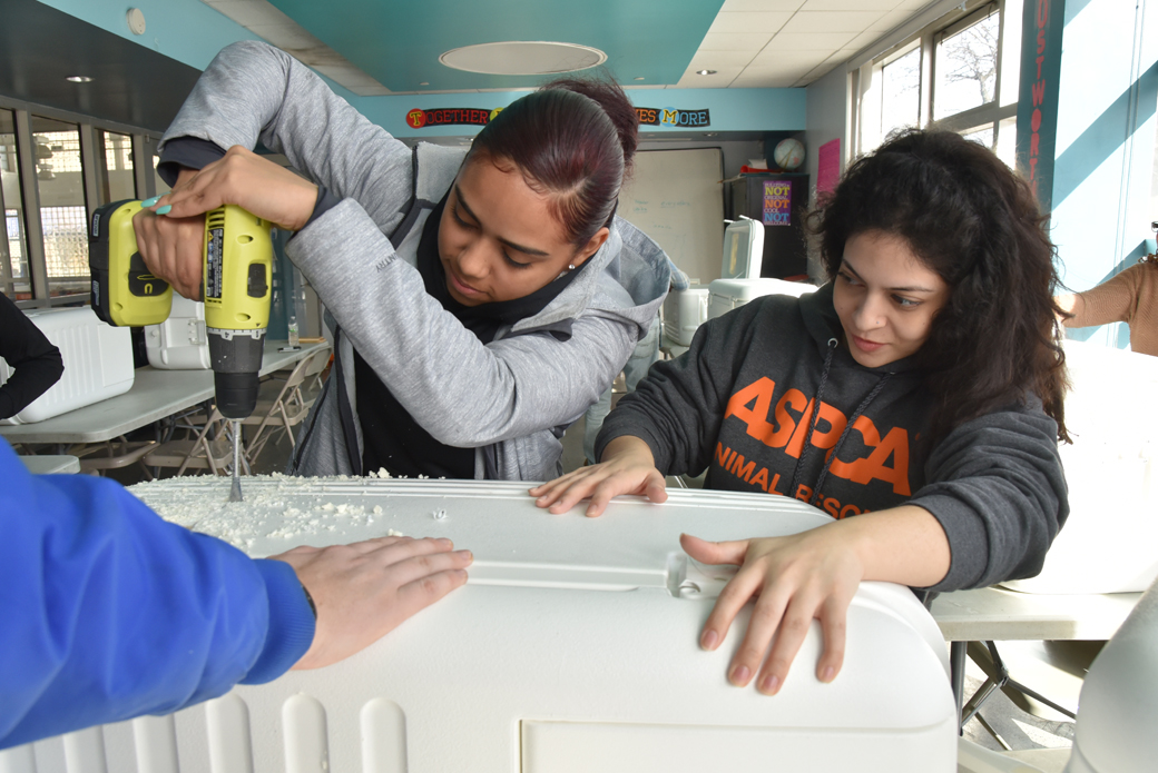 ASPCA's Isadora Peraza-Martinez steadies a cooler while Angelica Ramos drills holes