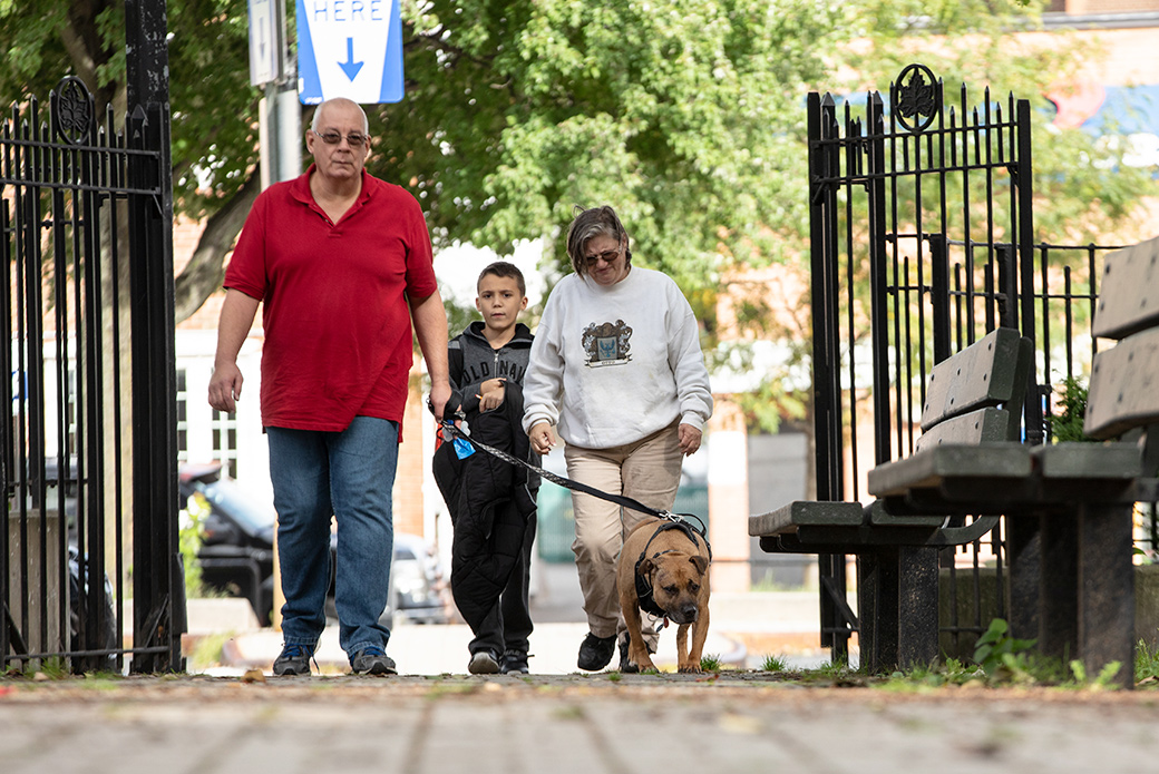 Robert, Maria and their grandson walk Orson through their neighborhood in Queens