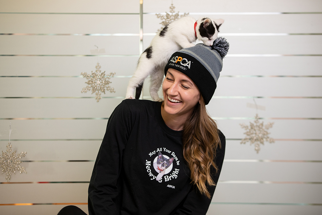woman with an ASPCA hat and a cat climbing on her