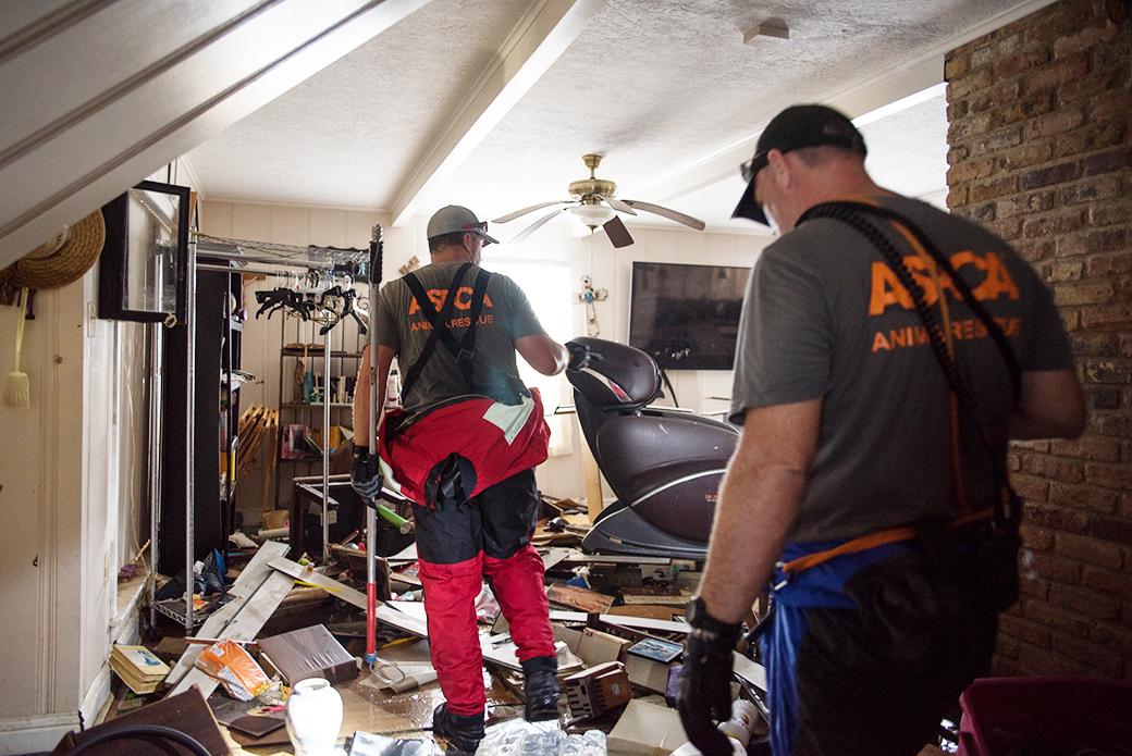 Responders carefully navigate through a damaged home
