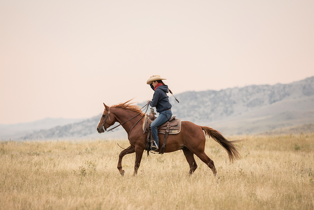 a woman riding a horse in the western style