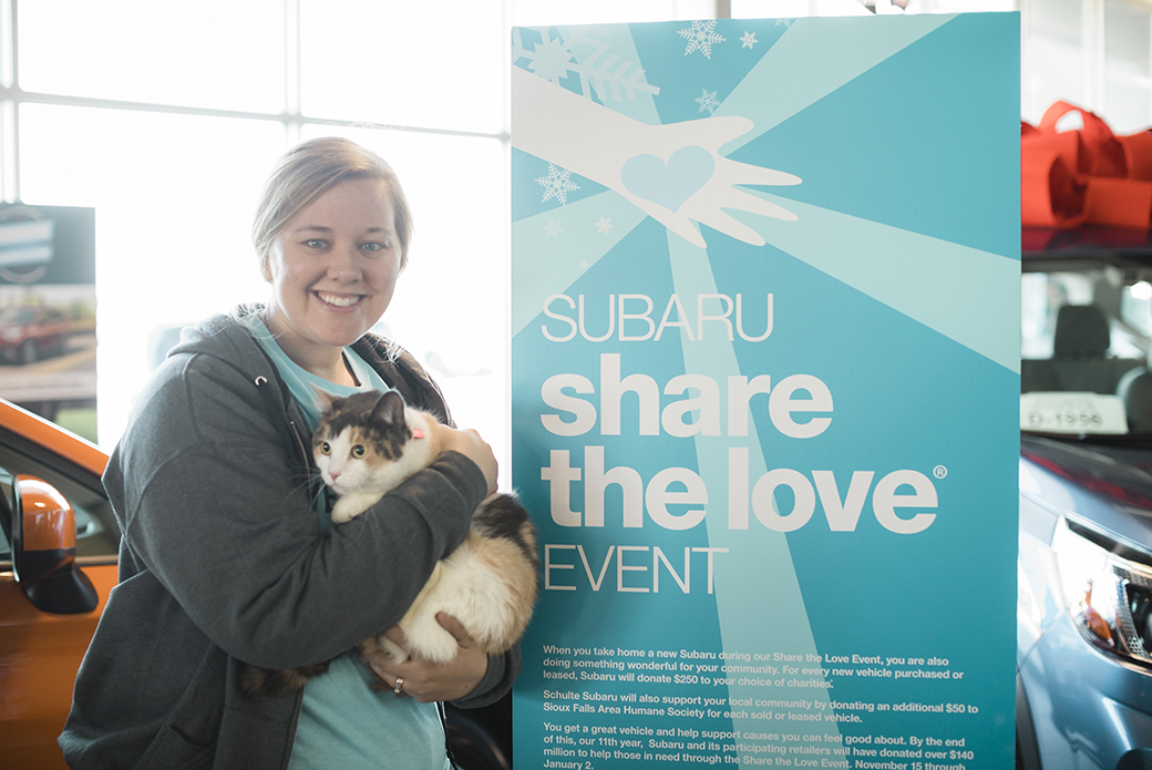 a woman holding a cat near a share the love sign