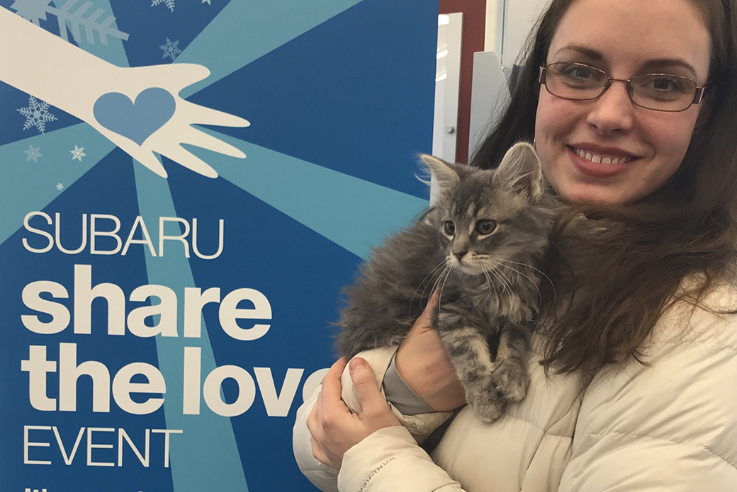 a woman with her cat at a subaru share the love event