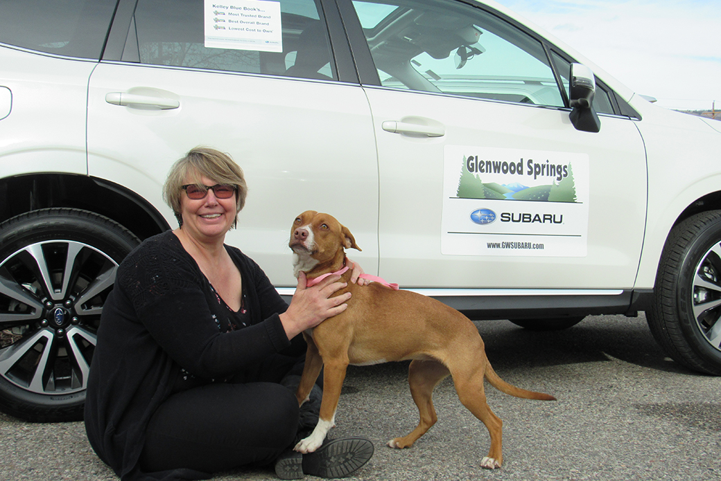 a woman and her dog at a subaru share the love event