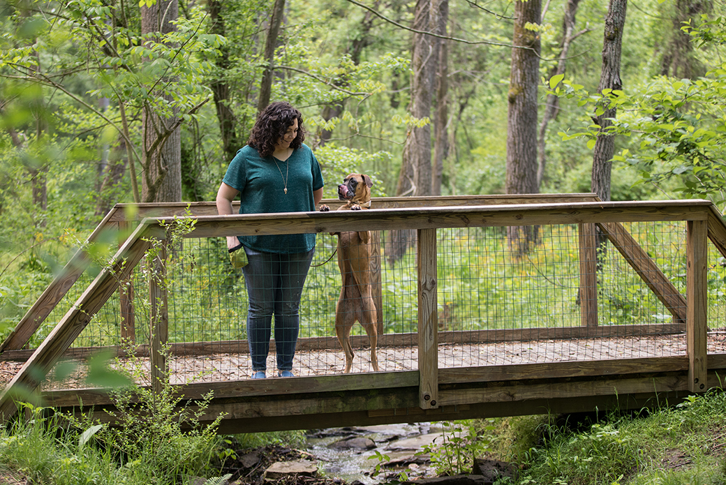 a woman with her dog on a wooden bridge