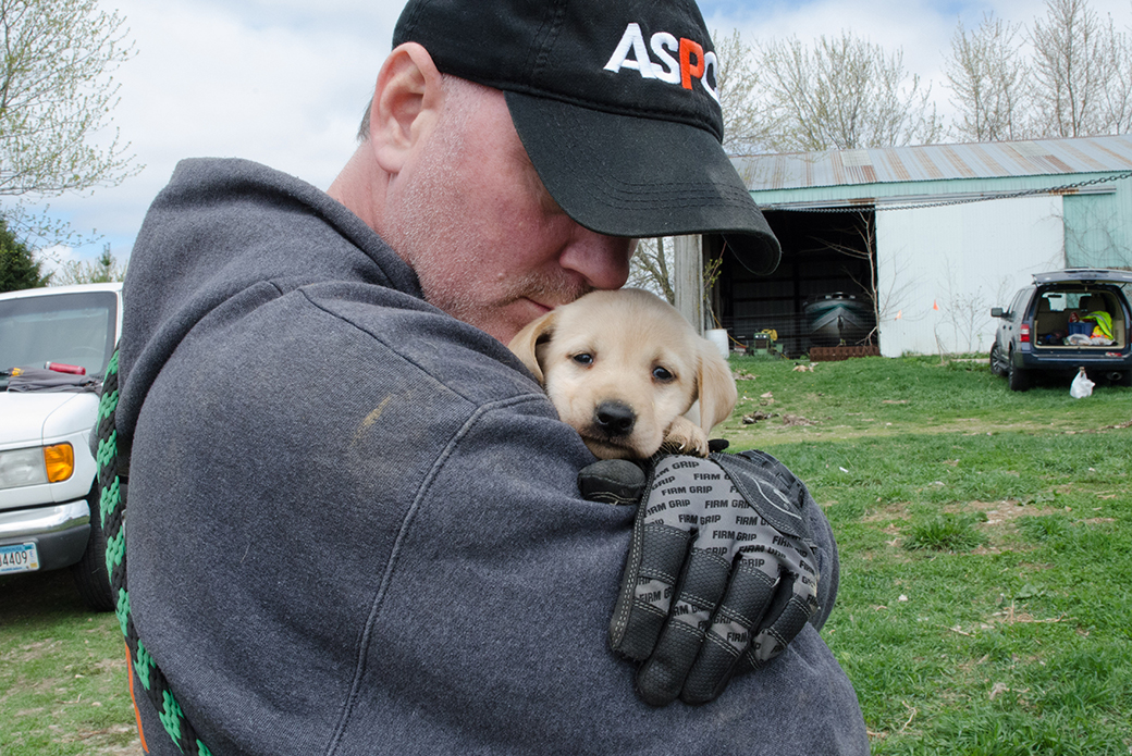 Here, an ASPCA responder comforts a young puppy during the rescue.