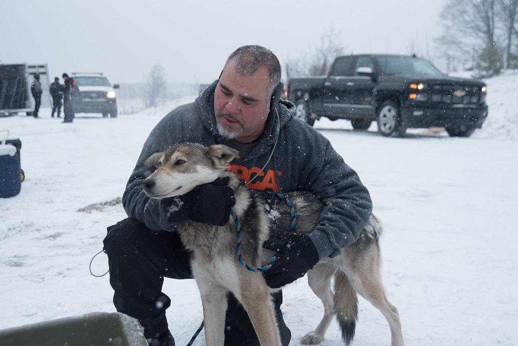 ASPCA volunteer hugging a dog