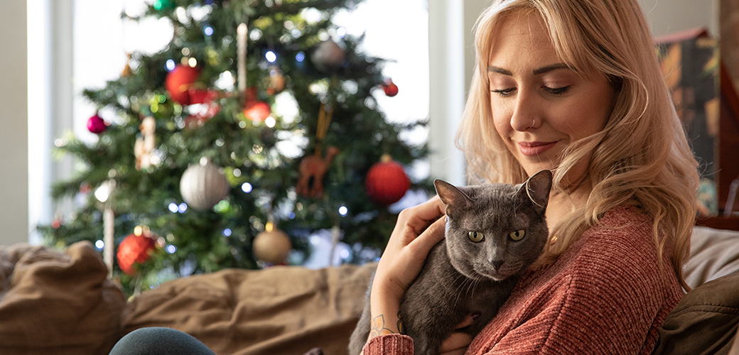 a woman holding a cat sitting on a couch in front of a christmas tree