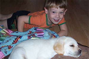 Young boy laying on floor next to puppy