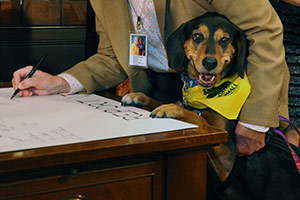 Dog standing at desk next to politician