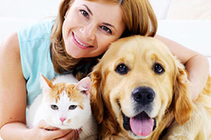 Red haired woman smiling with cat and dog