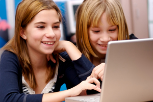 young girls look at computer screen