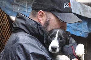ASPCA responder holds black and white puppy
