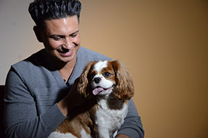 DJ Pauly D holding a small dog
