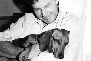 Black and white photo of man holding dachshund