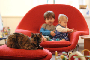 Cat laying on chair with two kids in the background