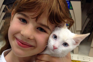Little girl holds white cat