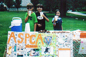 Three kids next to a lemonade stand raising money for the ASPCA