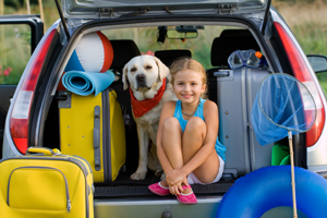 Little girl sitting in back of van with yellow lab