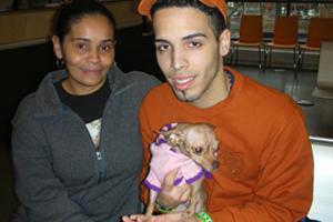 Man and woman hold tan chihuahua