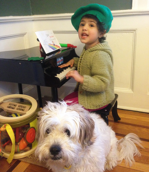 Young girl playing on a small piano with her dog sitting next to her