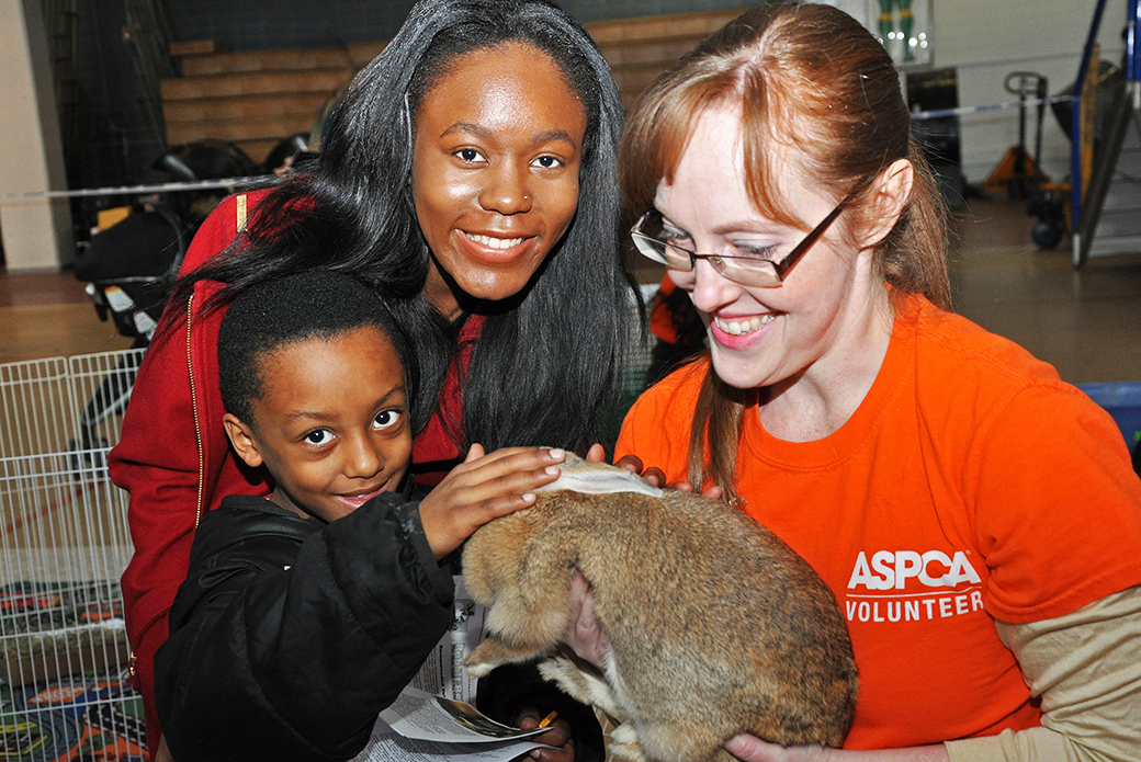 ASPCA Volunteer Robyn Shepherd hands Yvonne to her new family, Jazavia and Tyler.