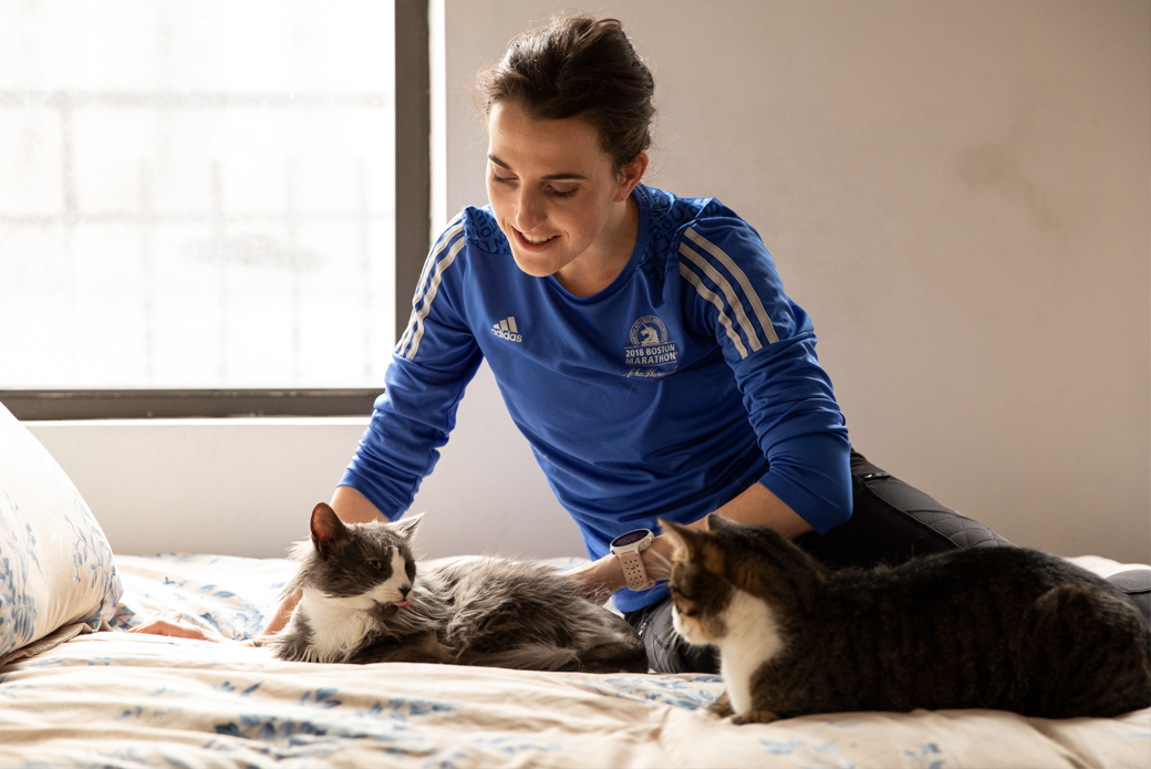 Woman sitting on bed with two cats