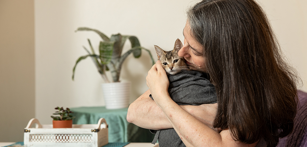 a woman hugging a cat wrapped in a blanket