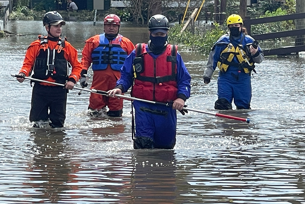 Responders wading through water