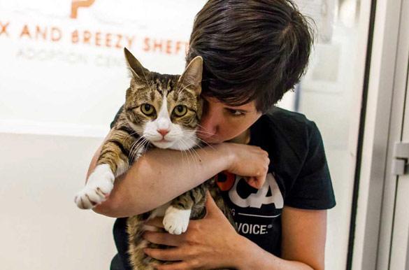 Adi, Feline Behavior Counselor at the ASPCA Adoption Center, hugging Robbie