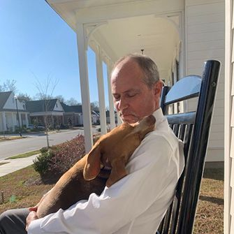 Daisy being held by outside on the front porch